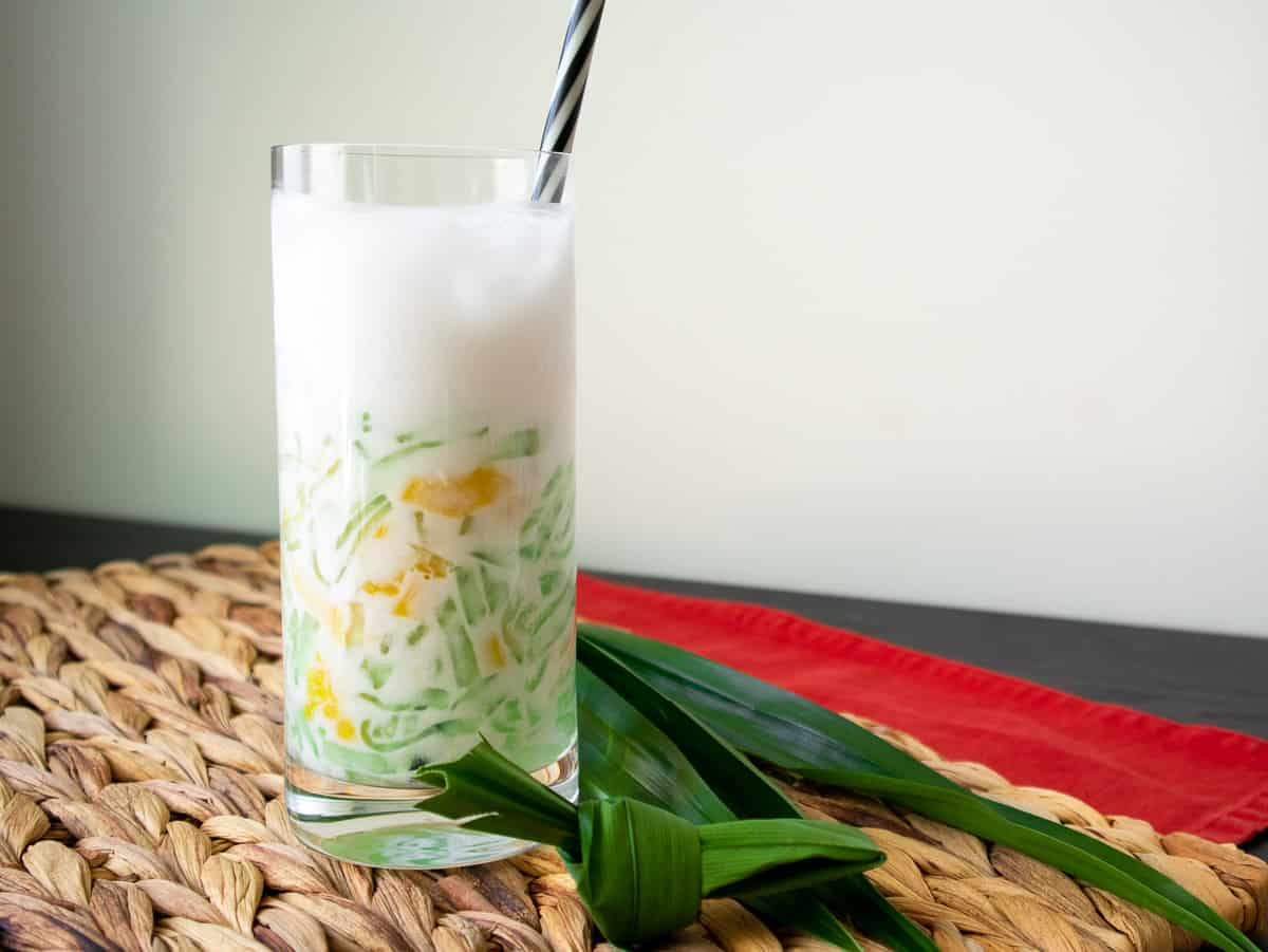 A glass of lodchong singapore in coconut milk with a straw in the glass and pandan leaves on the side.