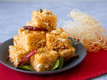 A plate of sweet and sour crispy noodle squares with dried chilies and makrut lime leaves garnishes.