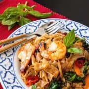 """A plate o drunken noodles with shrimp with text overlay """"pad kee mao drunken noodles"""""""