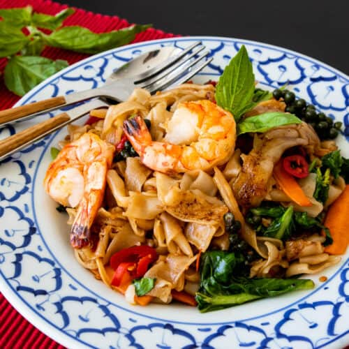 A plate of drunken noodles with shrimp on red placemat