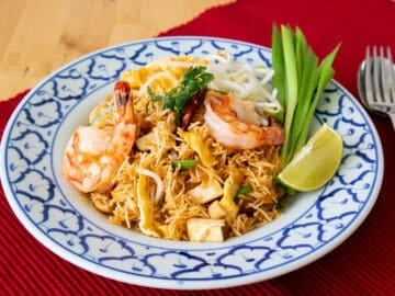 A plate of crispy noodles with shrimp, garlic chives, and a wedge of lime.