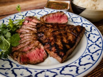 A plate of grilled steaks, some thinly sliced with dipping sauce and sticky rice on the side.