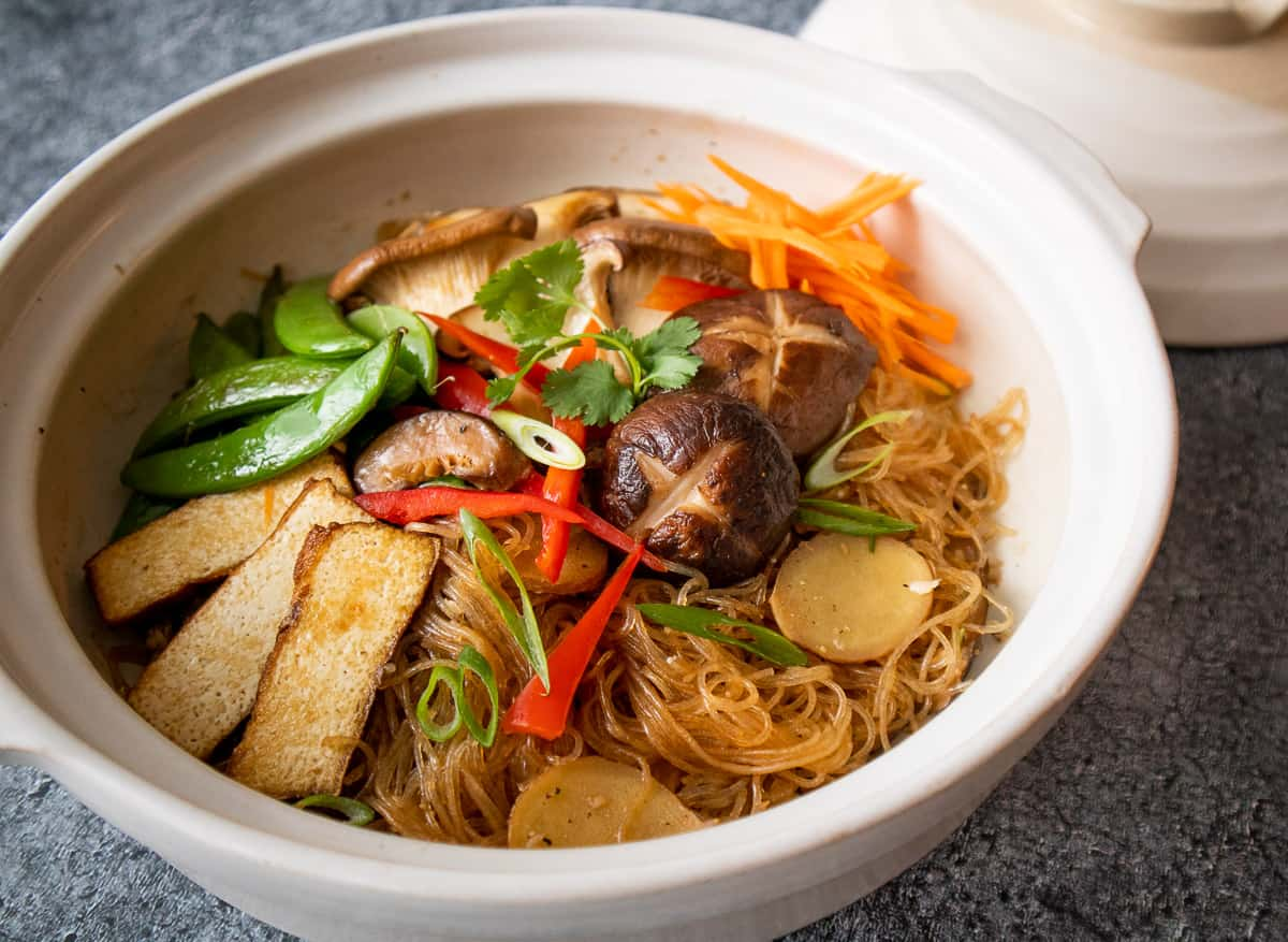 Glass noodles in clay pot topped with tofu, mushrooms, sugar snap peas, red pepper and carrots